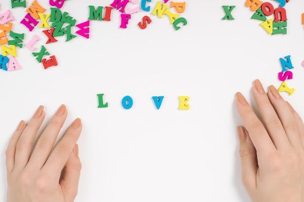 Vrouwelijke handen leggen het woord liefde uit gekleurde letters
