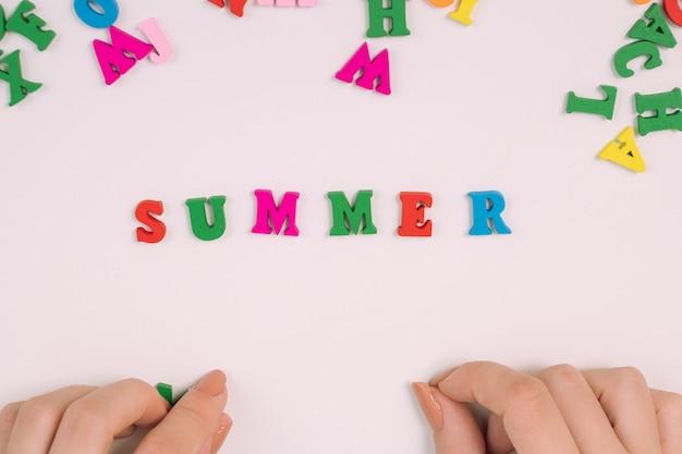 Vrouwelijke handen leggen het woord zomer uit gekleurde letters