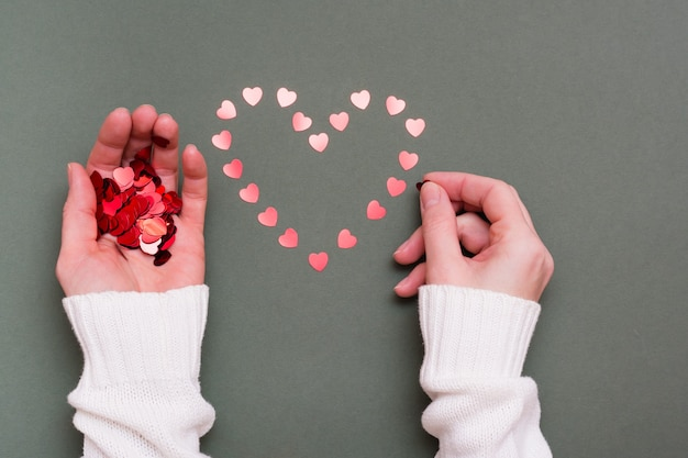 Vrouwelijke handen leggen uit kleine harten een hartvorm op een groene achtergrond