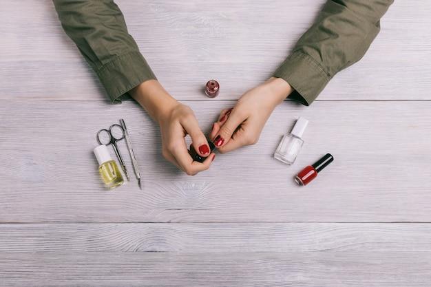 Vrouwelijke handen maken manicure en verfspijkers met rode lak