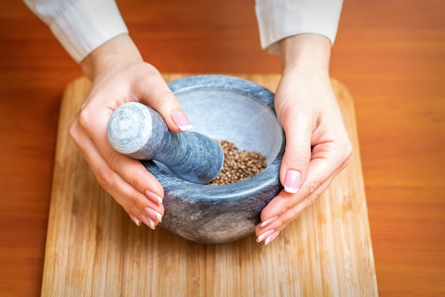 Vrouwelijke handen malen droge peperkruiden in mortel op een houten keukenbord