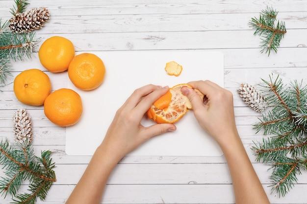Vrouwelijke handen mandarijn peeling op witte houten tafel met fir takken en kegels. close-up, top uitzicht.