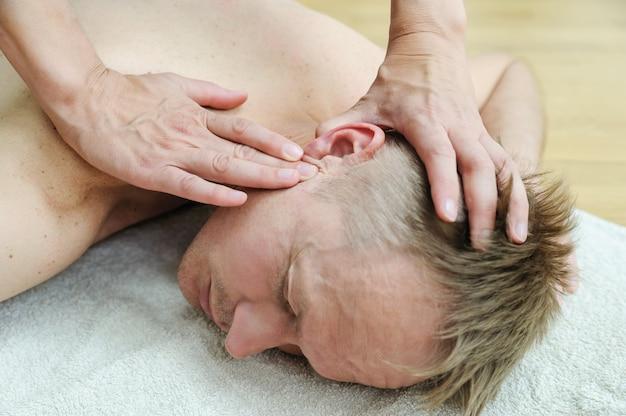 Vrouwelijke handen masseren het oor van de man na acupunctuur