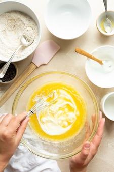 Vrouwelijke handen mengen eieren, suiker, olie en yoghurt in glazen kom, bovenaanzicht. stap voor stap recept voor het koken van een cake.
