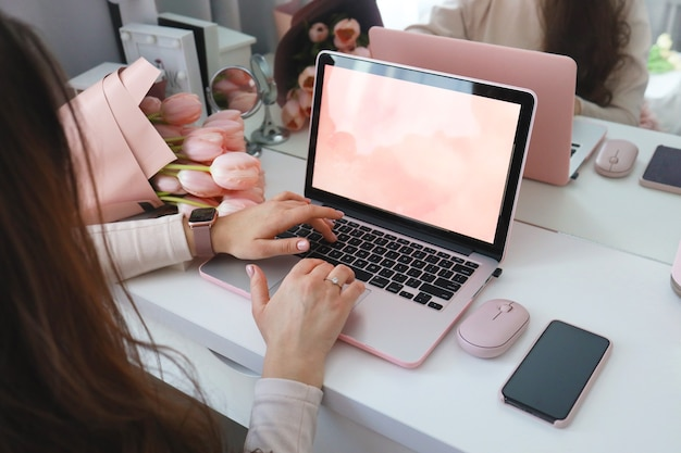 Vrouwelijke handen met behulp van laptop. vrouwelijk bureau werkruimte thuiskantoor mock-up met laptop, roze tulp bloemen boeket, smartphone en roze accessoires.