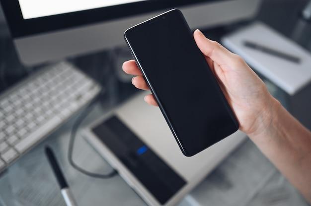 Vrouwelijke handen met behulp van slimme telefoon in interieur werkplek, freelance zakenvrouw met behulp van mobiele telefoon op kantoor, werken vanuit huis met behulp van slimme telefoon en notebook computer. quarantaine op afstand