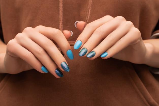 Vrouwelijke handen met blauw spijkerontwerp op bruin stoffenoppervlak.