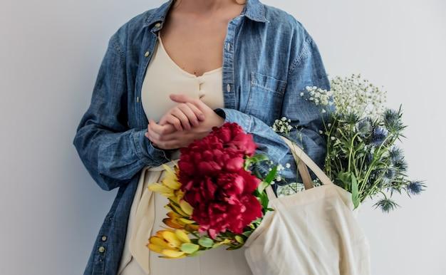 Vrouwelijke handen met boeket van pioenrozen, babys breathand en leucadendron
