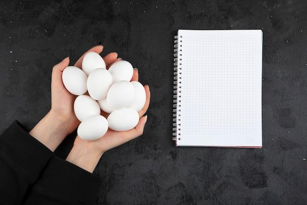 Vrouwelijke handen met bos van rauwe eieren op zwarte achtergrond.