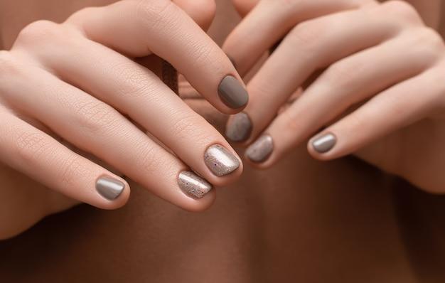 Vrouwelijke handen met bruin spijkerontwerp op bruin stoffenoppervlak.