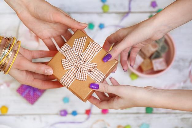 Vrouwelijke handen met cadeau close-up