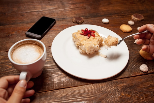 Vrouwelijke handen met cake en kopje koffie in café