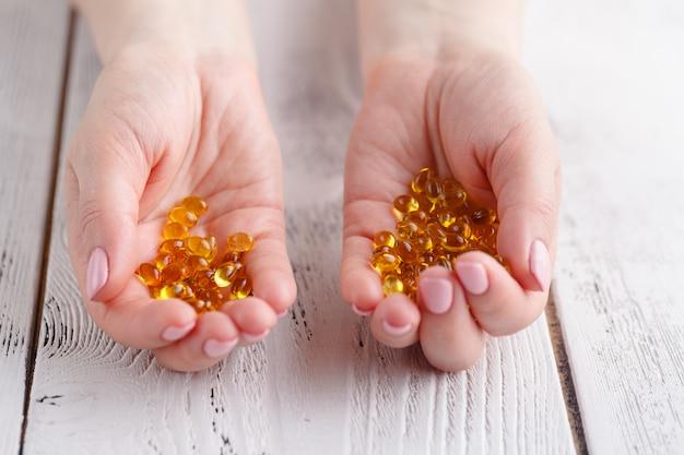 Vrouwelijke handen met capsules van visolie en vitamine e.