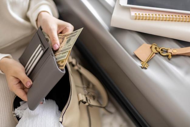 Vrouwelijke handen met contant geld dollars in portemonnee met kaarten klaar voor reizen, vakantie of zakenreis