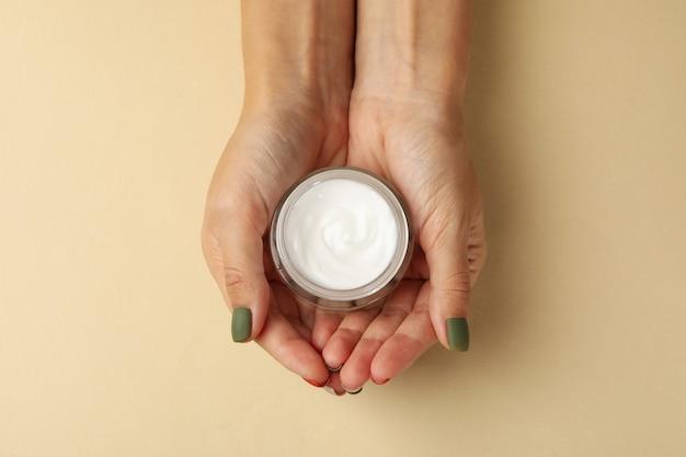 Vrouwelijke handen met cosmetische crème geïsoleerd