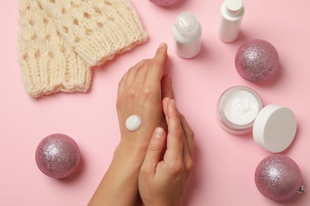 Vrouwelijke handen met cosmetische crème op roze achtergrond met kerstaccessoires