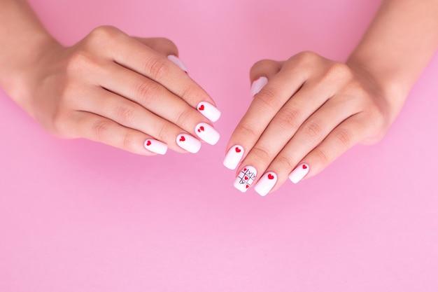 Vrouwelijke handen met creatieve manicurespijkers, witte gellak, hartenontwerp, op roze achtergrond