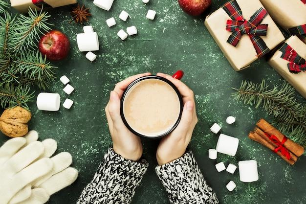 Vrouwelijke handen met cup met warme chocolademelk en verschillende attributen van vakantie op een groene ondergrond. bovenaanzicht