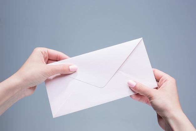 Vrouwelijke handen met de envelop tegen de grijze achtergrond