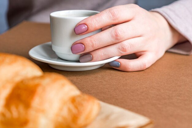 Vrouwelijke handen met de kop van de manicureholding van koffie en het eten van croissant. ontbijt in franse stijl