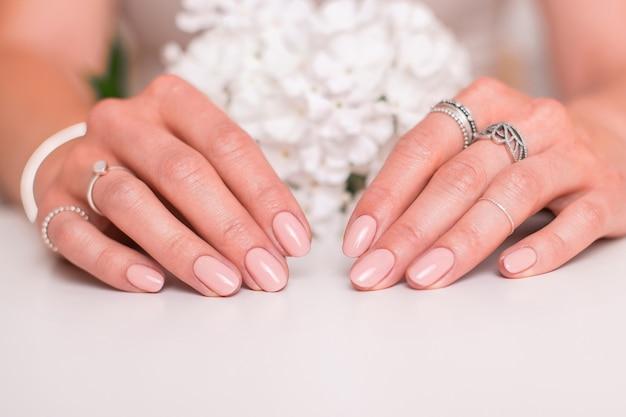 Vrouwelijke handen met de nagels van de huwelijksmanicure
