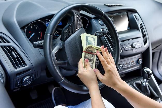Vrouwelijke handen met dollarbundel op stuurwiel close-up. omkoping en corruptie