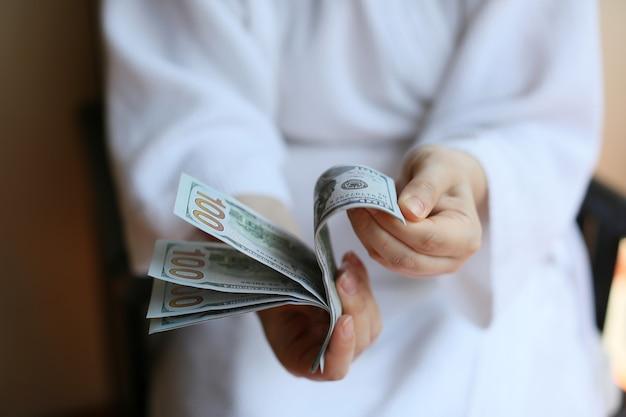 Vrouwelijke handen met dollars op een neutrale achtergrond