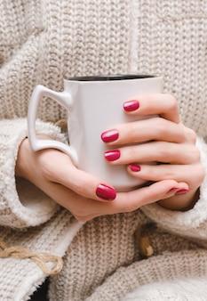 Vrouwelijke handen met donker roze nagelontwerp.
