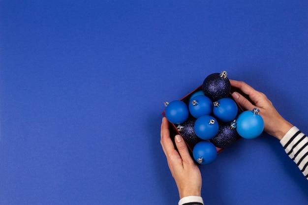 Vrouwelijke handen met doos met blauwe kerstbal ballen op blauwe achtergrond