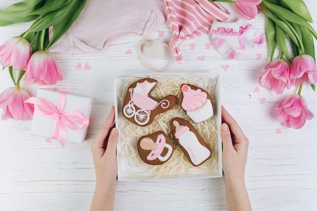Vrouwelijke handen met doos met cookies. een samenstelling voor pasgeborenen