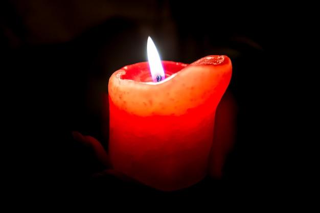 Vrouwelijke handen met een brandende kaars in de duisternis, knuffelen het rond