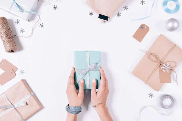Vrouwelijke handen met een geschenkdoos met lintmong kerstversiering