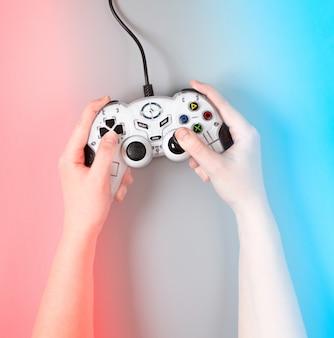 Vrouwelijke handen met een joystick van het spel op blauwe en rode ondergrond.