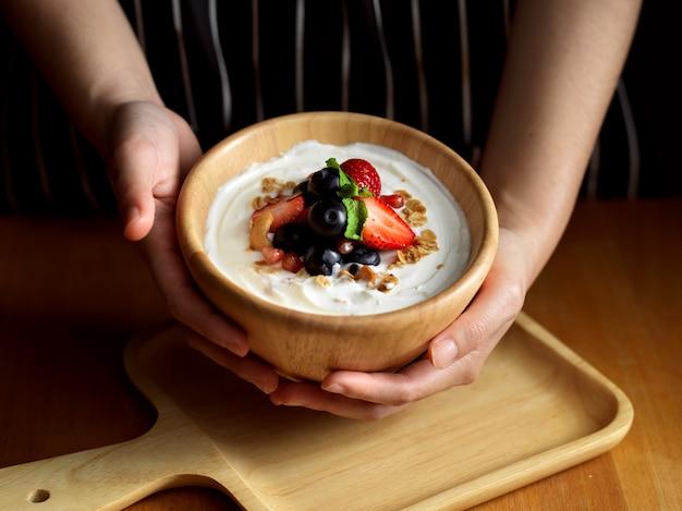 Vrouwelijke handen met een kom muesli met griekse yoghurt en verse bessen