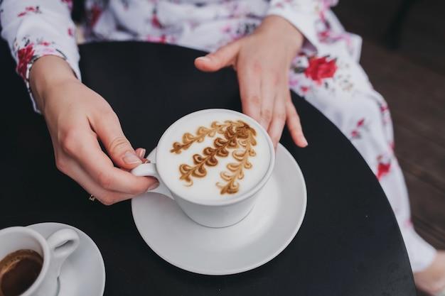 Vrouwelijke handen met een kopje koffie met boven tafel, bovenaanzicht