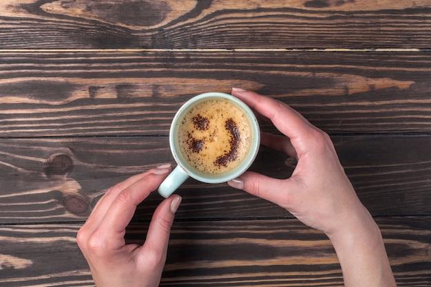 Vrouwelijke handen met een kopje koffie met schuim boven een houten tafel. met hagelslag