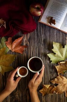 Vrouwelijke handen met een kopje warme thee en een mok met honing. thee, honing, herfstbladeren, een boek en een wollen trui op een rustieke achtergrond. herfst gezellige sfeer. herfst achtergrond. plat liggen. verticaal