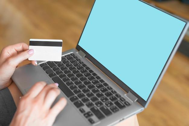 Vrouwelijke handen met een laptop en een creditcard.