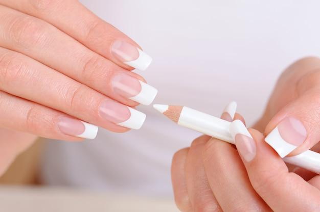 Vrouwelijke handen met een manicure wit potlood