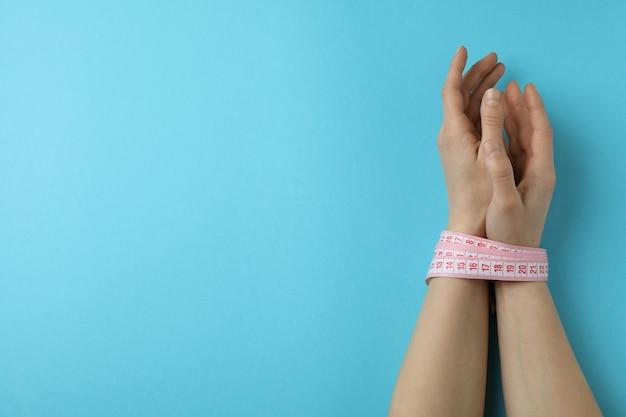 Vrouwelijke handen met een meetlint op blauw