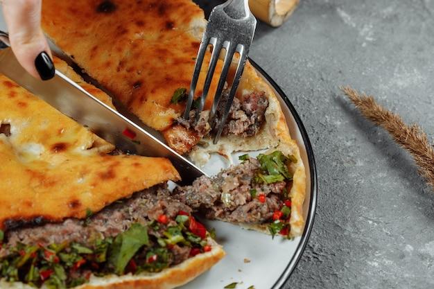 Vrouwelijke handen met een mes en een vork snijden khachapuri met lam en chili. georgisch nationaal eten.