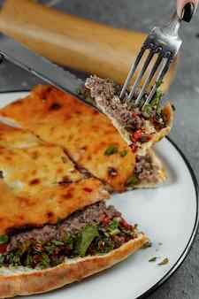 Vrouwelijke handen met een mes en een vork snijden khachapuri met lamsvlees en chili. georgisch nationaal eten.