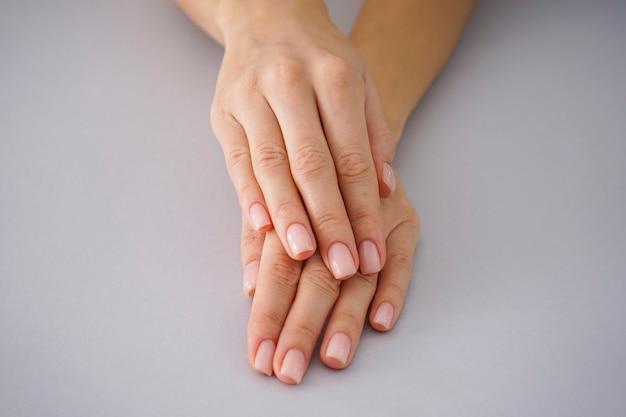 Vrouwelijke handen met een mooie manicure op een grijze achtergrond.