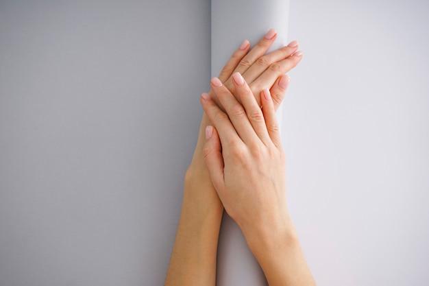 Vrouwelijke handen met een mooie manicure op een witgrijze achtergrond.