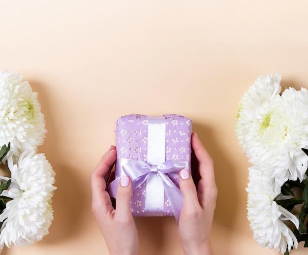 Vrouwelijke handen met een paarse doos met witte bloemen eromheen op een lichtgele achtergrond