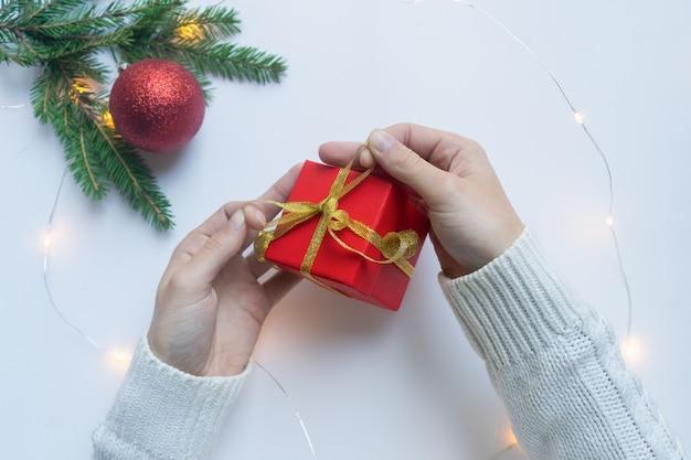 Vrouwelijke handen met een rode geschenkdoos gebonden met een gouden lint. concept van geschenken voor kerstmis en nieuwjaar.