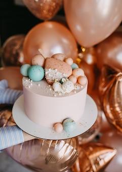 Vrouwelijke handen met een roze cake op een houten bord voor een verjaardagsfeestje versierd met chocoladespeelgoed
