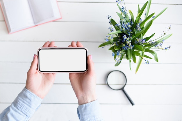 Vrouwelijke handen met een smartphone. wit leeg scherm. tafel met laptop en bloemen