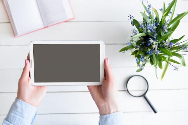 Vrouwelijke handen met een tablet. zwart leeg scherm. tafel met laptop en bloemen