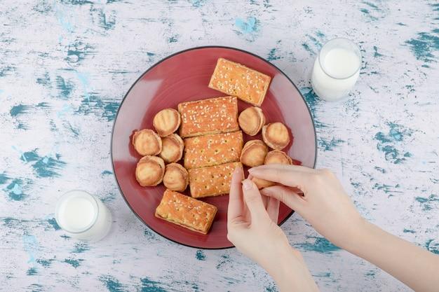 Vrouwelijke handen met een zandkoek noten met gecondenseerde melk.